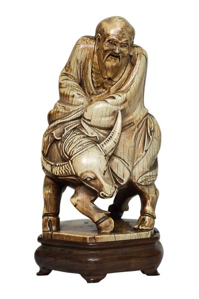 """Raríssima e magnífica escultura em marfim chinês, possivelmente anterior ao séc. XVIII, representando """"Monge sobre búfalo"""". Base sextavada em madeira. Alt.: 25cm. Reproduzido com foto no catálogo."""