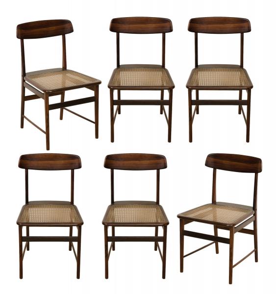 """SERGIO RODRIGUES (1927-2014). Seis cadeiras em jacarandá ditas """"Lucio Costa"""" (circa 1956). Espaldar com travessa ligeiramente encurvada. Montantes e pernas torneados. Amarrações com travessas retas. Assento em palhinha. Estas cadeiras encontram-se reproduzidas na pág. 253 do livro do artista publicado pela """"Icatu"""". Reproduzido com foto no catálogo."""