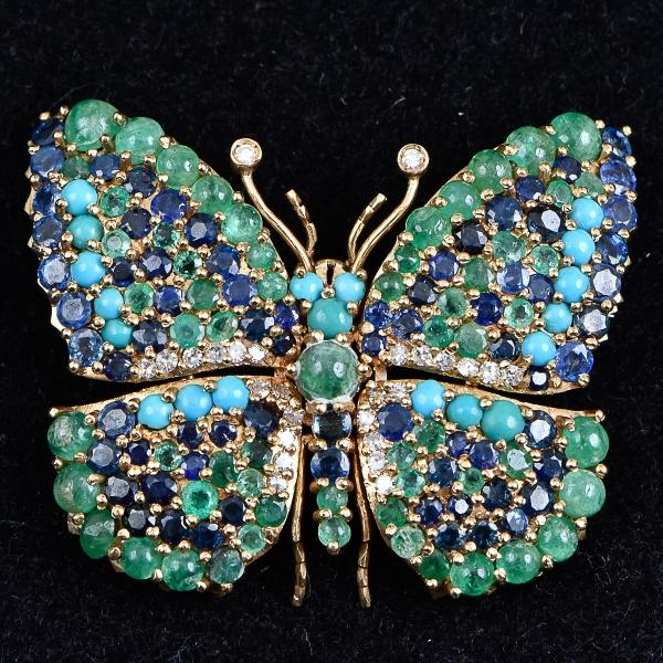 Extraordinário broche art nouveau no feitio de borboleta em ouro 18k com 26 brilhantes, esmeraldas e turquesas cabochon, e safiras redondas. Medida: 5,5 X 4,5. Peso: 40,3g.