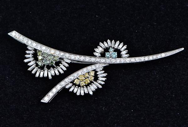 Magnífico broche no feitio de ramo de flores, em ouro branco com 44 brilhantes lapidação baguete, 18 brilhantes coloridos e 52 diamantes. Comp.: 9cm. Peso: 17,4g.