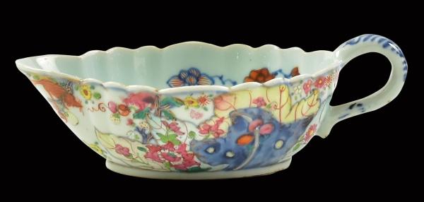 """Raríssima molheira em porcelana chinesa da """"Cia das Índias"""", séc. XVIII, período Qianlong (1736-1795), dita """"Folha de tabaco"""", decorado em rica policromia com farta vegetação floral, frutos, fênix e esquilos. Borda ondulada. Interior esmaltado com flores. Medida: 18 X 11. Reproduzido com foto na capa do catálogo. (Em função da fragilidade, este lote só poderá ser enviado para fora do estado através de transportadora especializada)."""
