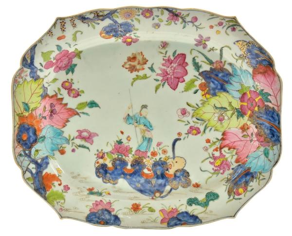 """Raríssima travessa retangular com cantos chanfrados em porcelana chinesa da """"Cia das Índias"""", séc. XVIII, período Qianlong (1736-1795), dita """"Folha de tabaco"""", decorado em rica policromia com farta vegetação floral, frutos, fênix e divindade """"Kuan Yin com cajado na floresta"""". Borda ondulada. Medida: 42 X 35. Reproduzido com foto na capa do catálogo. (Em função da fragilidade, este lote só poderá ser enviado para fora do estado através de transportadora especializada)."""