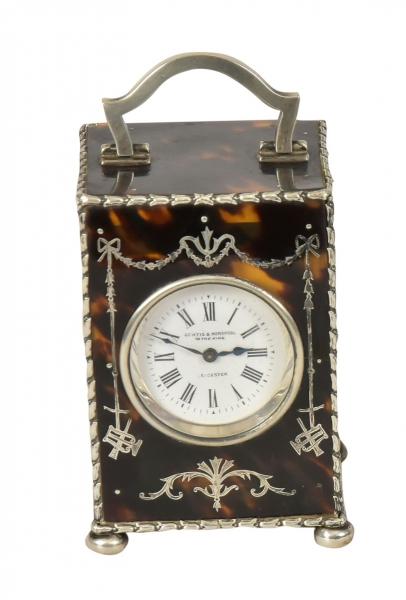"""CURTIS & HORSPOOL. Raro carriage clock inglês com caixa em casco de tartaruga polido marchetado no estilo neoclássico. Base e guarnições em prata do período """"Edward VII"""", contraste da cidade de """"Londres"""" de 1906. Mostrador esmaltado com designação do fabricante """"Curtis & Horspool to the King - Leicester"""". Alt.: 9,5cm. Larg.: 6cm. Prof.: 5,5cm. Prateiro """"W.C"""". Reproduzido com foto no catálogo."""
