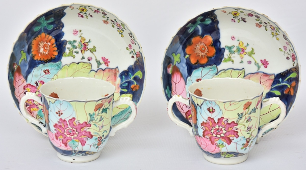 """Par de raríssimas """"Loving Cups"""" com pires em porcelana chinesa da """"Cia das Índias"""", séc. XVIII, período Qianlong (1736-1795), dita """"Folha de tabaco"""", decorado em rica policromia com farta vegetação floral. Borda ondulada. Diam.: 14cm. Alt.: 8cm. (Um pires com fio de cabelo). Reproduzido com foto no catálogo. (Em função da fragilidade, este lote só poderá ser enviado para fora do estado através de transportadora especializada)."""