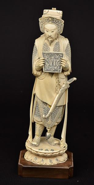 """Figura esculpida em marfim, representando """"Guardião do Templo do Imperador com papiro sobre flor de lótus"""". Base em madeira. Apresenta inscrições na base e marca de atelier no fundo. Alt.: 30,5cm. China - 1900. Reproduzido com foto no catálogo."""