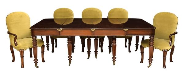 """Mesa elástica de jantar em mogno com 3 tábuas de extensão, estilo """"Inglês"""", séc. XIX. Extremidades de correr sobre estrutura suplementar. Pernas torneadas com gomos e canelados. Pés de rodinha. Guarnições laterais de encaixe em bronze dourado. Alt.: 81cm. Medida com as 3 tábuas: 3,00 X 1,50. Medida sem tábuas de extensão: 1,20 X 1,50. Acompanham 8 cadeiras de braço também em mogno estilo """"Georgeano"""". Braços e pernas arqueados. Pés de espátula. Assento e encosto forrados em veludo verde musgo. Reproduzido com foto no catálogo."""