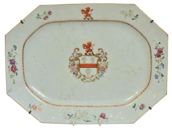"""Travessa brasonada retangular com cantos chanfrados em porcelana chinesa da """"Cia da Índias"""", séc. XVIII, período """"Qianlong"""" (1736 - 1795), esmaltagem """"Família Rosa"""", tendo ao centro """"Brasão de Armas"""" com cores heráldicas. Borda com ramos e flores salpicadas. Medida: 37 X 28. Pertenceu à famosa coleção """"Nelson Muniz"""" (etiqueta no fundo). Reproduzido com foto no catálogo. (Em função da fragilidade, este lote só poderá ser enviado para fora do estado através de transportadora especializada)."""