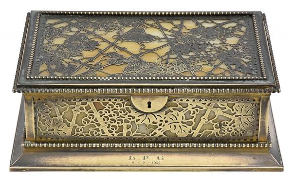 """TIFFANY STUDIOS - NEW YORK (CIRCA 1910/1920). """"Jewelry Box"""" em bronze dourado vazado decorado com ramos e folhas de parreira sobre pasta de vidro dita """"fravile glass"""". Medida: 22 X 15. Designer """"Louis Comfort Tiffany"""". Gravado no fundo. (Leve fio de cabelo na parte interna)."""