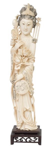 """Delicada figura esculpida em marfim, representando """"Divindade Kuan Yin com ventarola e ramo de flor de lótus na mão"""". Base em madeira entalhada e vazada. Alt.: 46cm. China - 1900. Reproduzido com foto no catálogo."""