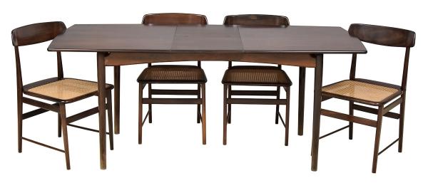 """SERGIO RODRIGUES (1927-2014). a) Mesa de jantar em jacarandá da década de 60. Borda ligeiramente arqueada e pernas torneadas afinando para baixo. Alt.: 75cm. Medida: 1,45 X 0,82. Apresenta cachet da famosa """"Oca Arquitetura Indústria e Comércio S.A."""". b) Seis cadeiras em jacarandá ditas """"Lucio Costa"""" (década de 60). Espaldar vazado com travessa ligeiramente arqueada. Pernas e amarrações retas e torneadas. Assento forrado em palhinha. Reproduzido com foto no catálogo."""