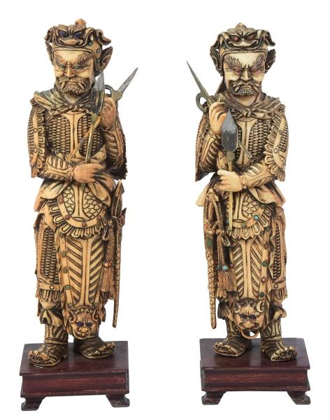 """Par de figuras esculpidas em marfim, adornadas com contas em coral e turquesa, representando """"Guardiões do Templo do Imperador"""". Base em madeira. Alt.: 23,5cm. China - 1900. Reproduzido com foto no catálogo."""