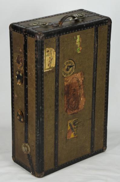 Antiga mala para viagem em madeira revestida com lona, arrematada em couro tacheado. Guarnições em m