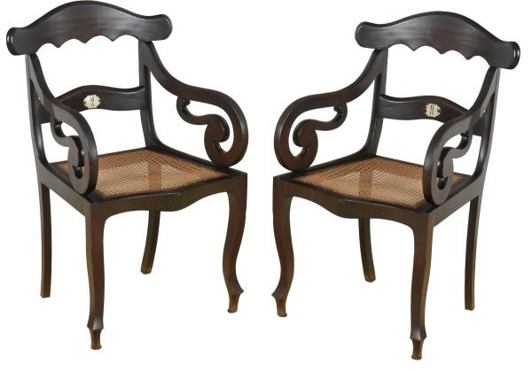 """THEATRO LYRICO (1851-1934). Par de raras cadeiras de braço em jacarandá, estilo """"neo-rococó"""", séc. XIX (circa 1860). Espaldar vazado com 2 travessas onduladas, sendo a central com placa de identificação em metal esmaltado de localização do lugar na plateia (""""B17 e M5""""). Braços encurvados revirados para dentro. Pernas arqueadas. Pés de cachimbo. Assento em palhinha. Cadeira idêntica encontra-se reproduzida na pág. 287 do livro """"Antiguidades Brasileiras por Paulo Affonso de Carvalho Machado"""". Reproduzido com foto no catálogo."""