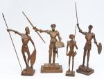 """Quatro figuras de """"Dom Quixote"""" esculpidos em madeira clara. Alt. do maior com a lança: 53cm. (Um escudo de 1 figura e chapéu de 2 figuras com lascado)."""