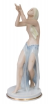 """ASSINATURA ILEGÍVEL (ALEMANHA, 1930). Figura art deco em porcelana alemã policromada da marca """"Rosenthal"""", representando """"Dançarina com vestes azuis"""". Alt.: 24,5cm. Assinada e com marca no fundo. Reproduzido com foto no catálogo. (Em função da fragilidade, este lote só poderá ser enviado para fora do estado através de transportadora especializada)."""