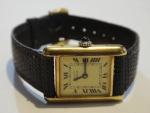 """CARTIER. Relógio feminino suíço de pulso da marca """"Cartier"""". Caixa em plaque d'or. Coroa em safira cabochon. Pulseira original em couro. Medida da caixa: 2,7 X 2,0. Movimento a corda. Funcionando."""